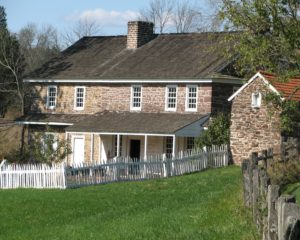 Daniel Boone Homestead's old stone house with a cover porch and white trimmed windows is surrounded by a white picket fence.