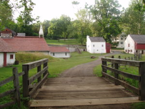 A small wooden bridge leads to a gravel path. In the distance sit a white building with a red roof and steeple and a white two story house, part of Hopewell Furnace National Historic Site.