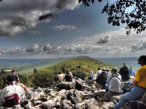 People sit on rocks with their backs to the camera, looking out over mountains as they watch for raptors during the fall hawk migration at Hawk Mountain Sanctuary.