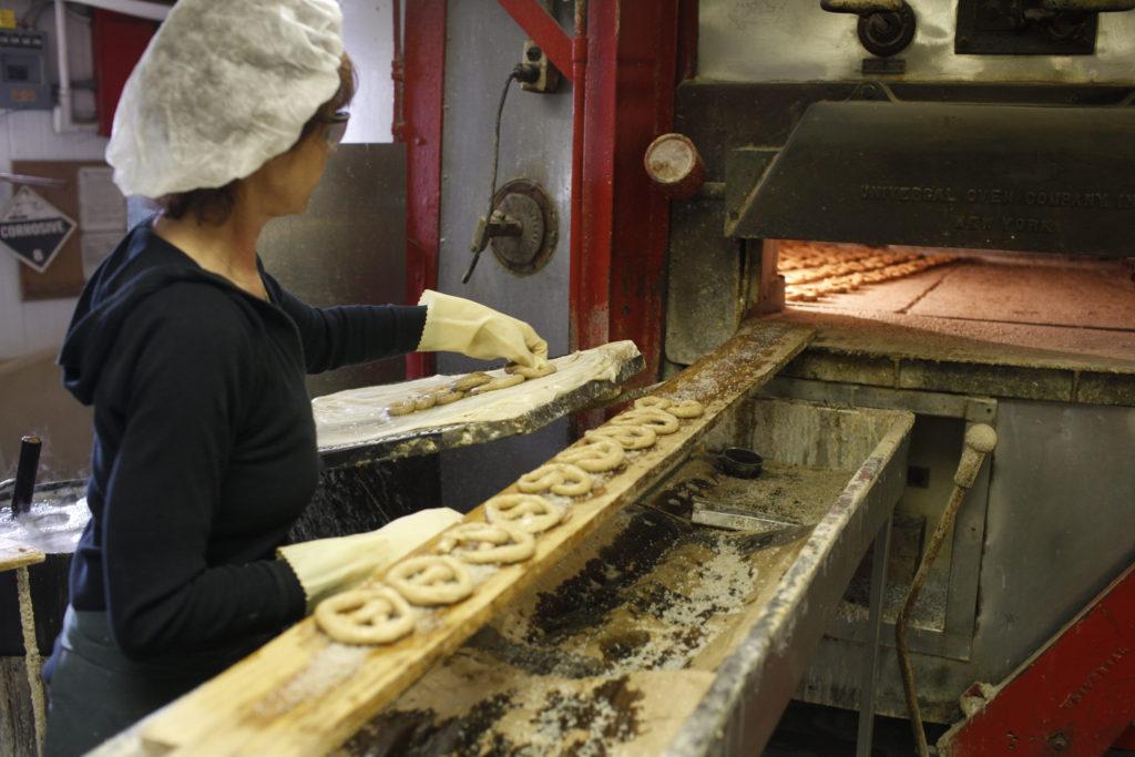 Woman puts fresh pretzels into the oven.